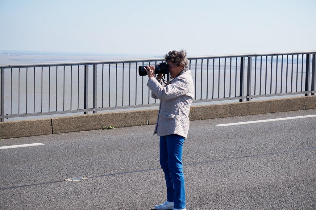 une dame utilise un appareil photo reflex